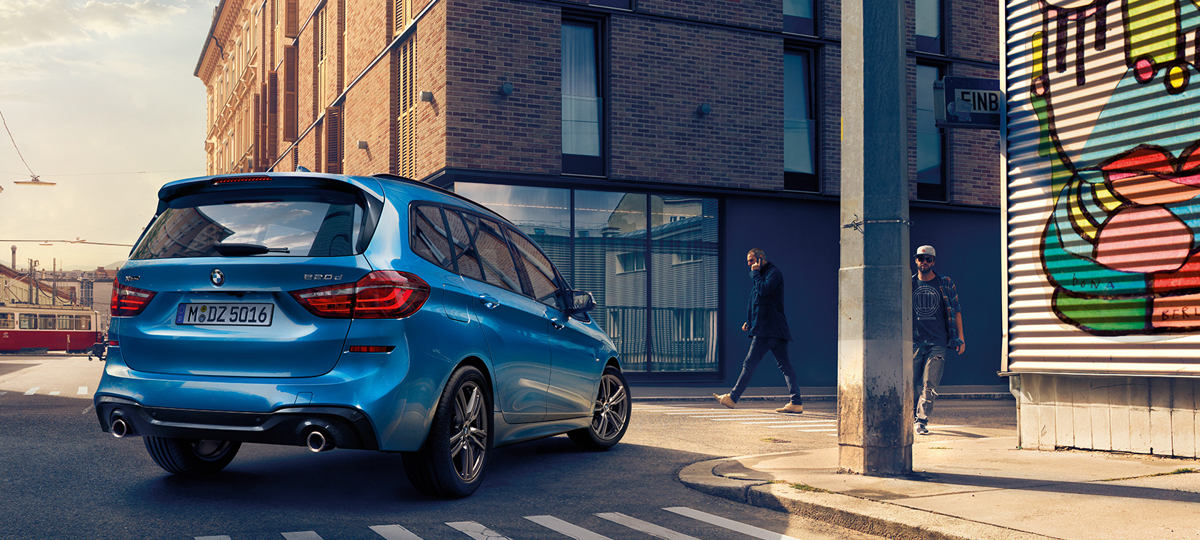Man next to BMW 2 Series Gran Tourer F46 2018 Estoril Blue metallic bird's-eye view parking on the street