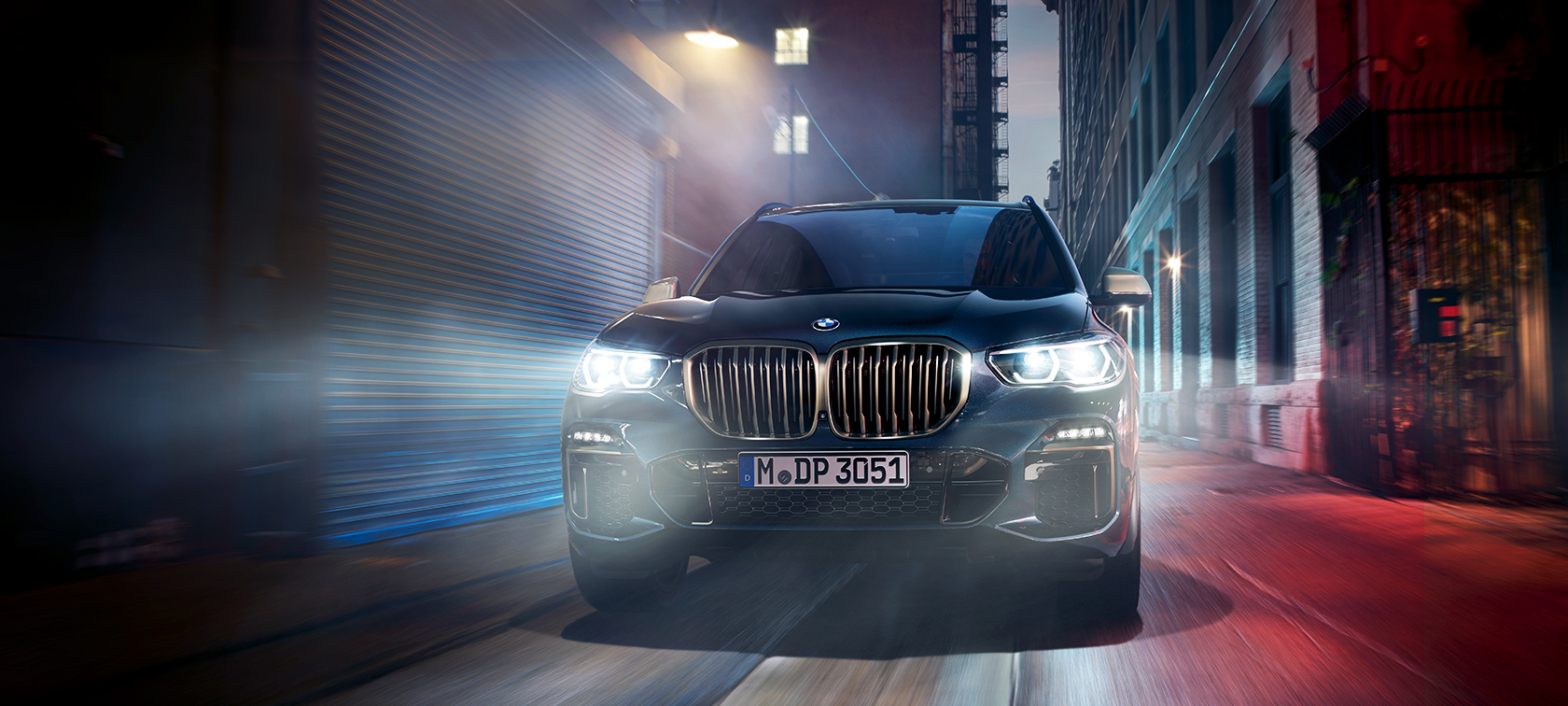 The BMW X5 M50d on a street in the city at night